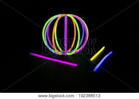 Ball bracvelet Glow sticks neon light fluorescent on back background. variation of different colored chem lights like a ball