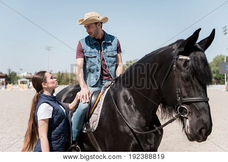 young man in cowboy hat sitting on horseback while holding hand on his girlfriend