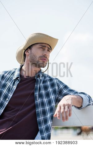 portrait of young man in cowboy hat and checkered shirt looking away and leaning on fence at ranch