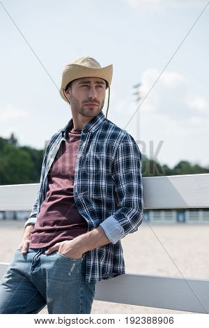 Young handsome man in cowboy hat looking away while leaning on fence at ranch