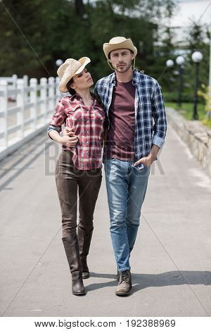 young couple in cowboy hats hugging and walking on ranch