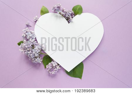 Heart frame with blossom lilac on violet background. Copy spase