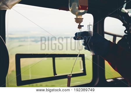 Silhouette of the hand of the doctor and infusion. Helicopter of the emergency medical service in flight. Czech Republic