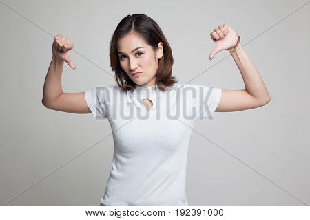 Unhappy Asian Girl Show Thumbs Down With Both Hands.