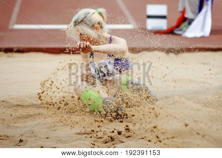 competition long jump women landing in sand a spray