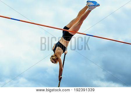 competition pole vault jumper female on blue sky background