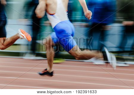 blurred motion man runners sprinters running on track stadium