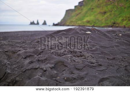 Detail of a black sand on the famous dark beach in the Icelandic town Vik with the rock cliffs in the ocean