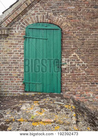 Old green wooden door on a brick barn in germany