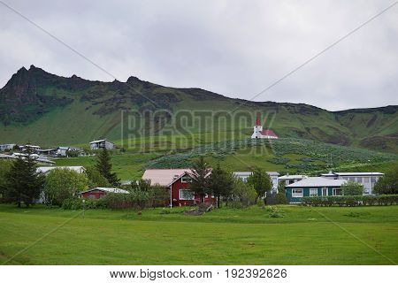 Icelandic town Vik with its famous church on the hill and a small town as a symbol of tranquil towns in Iceland