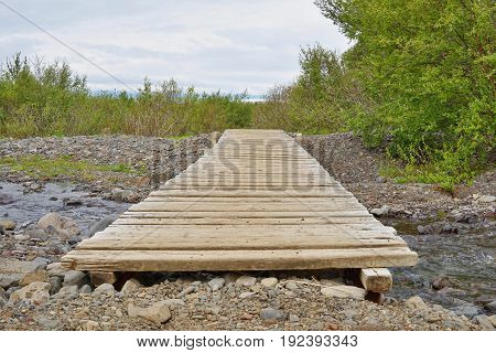 Detail of a wooden footbridge over a small creek in Icelandic mountains