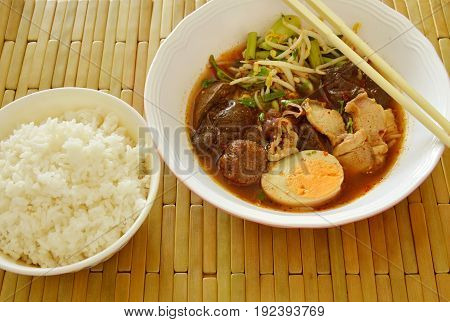 boiled pork entrails topping egg in brown soup eat couple with rice