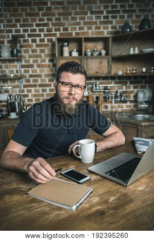 confident freelancer sitting at table with laptop and smartphone while looking at camera