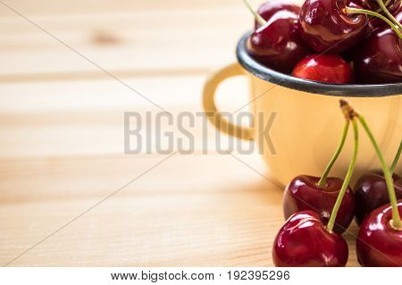 Red cherries in the yellow cup and on the wooden table in the right corner of the photo. Shallow depth of field