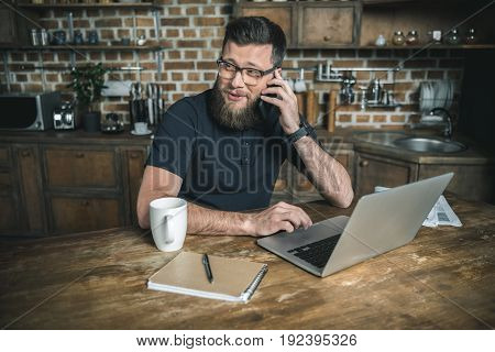 smiling bearded freelancer working with laptop and talking on smartphone in the kitchen