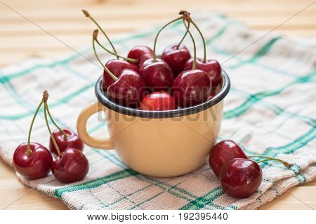 Red cherries in the yellow cup and on the wooden table covered with tablecloth. Object lit with natural light