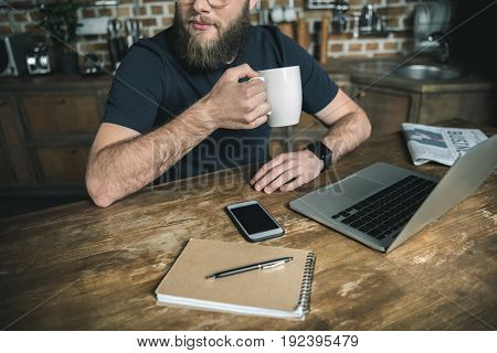 cropped view of bearded freelancer drinking coffee and working with laptop in home office