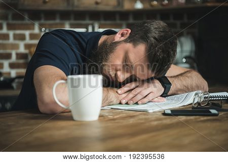 portrait of tired man sleeping on table with newspaper and coffee cup