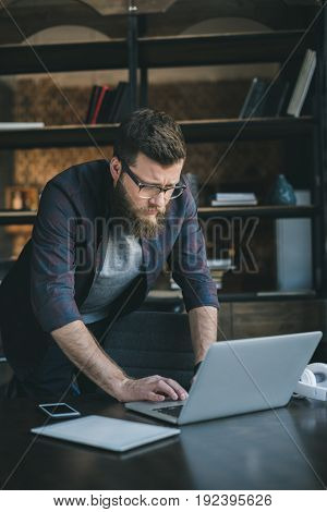 young casual bearded man in glasses using laptop at home