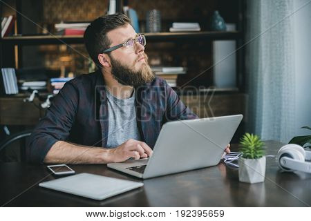 pensive bearded man typing on laptop while sitting at home