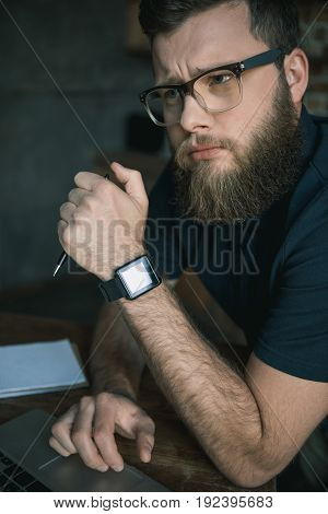 Portrait of young pensive bearded man in eyeglasses during work