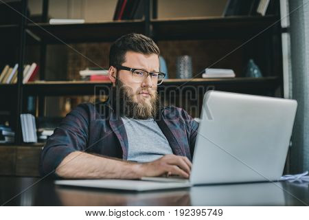 Portrait of young casual bearded man working on laptop at home