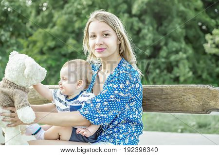 Pretty mather playing with baby boy outdoor on nature at sunny summer day