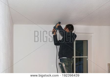 Young craftsman on a ladder with a Drilling machine.