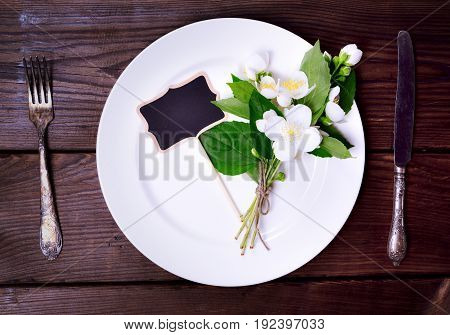 White round plate with iron knife and fork on a brown wooden background top view