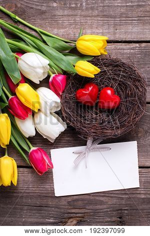 Little decorative hearts in nest empty tag and bright spring tulips flowers on wooden background. Selective focus. Flat lay. Place for text.