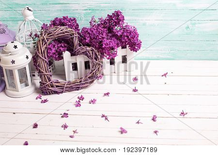 Fresh lilac flowers decorative heart and lanterns on white wooden background against turquoise wall. Selective focus. Place for text.