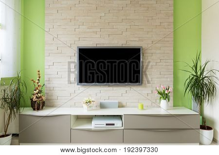 Modern living room interior - tv mounted on brick wall with black screen.