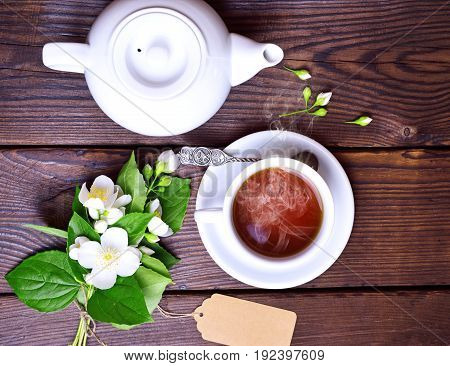 cup of black tea and a white brewer on a brown wooden background top view