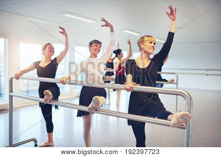 Group of adult women standing with hands up while doing gymnastics at handrail in ballet class.