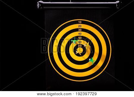 Magnetic green and yellow dart arrows on dart board. black background