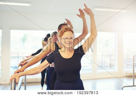 Senior adult woman standing with hand up performing a dance in ballet class.