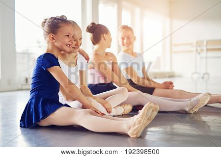 Little Girls Smiling And Embracing In Ballet Class