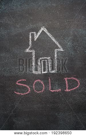 House with sold word drawn with chalk on blackboard
