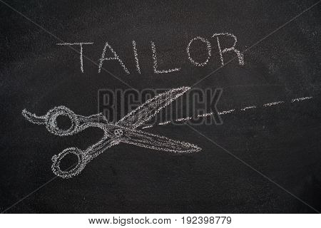 Scissors with cut line and tailor word drawn with white chalk on blackboard