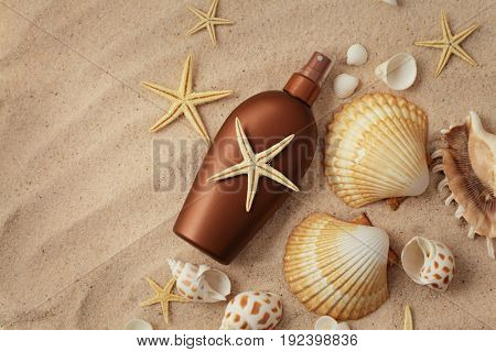 suntan lotion bottle and seashells on the sand beach