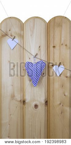 Three hearts with clothes pegs on a cord on wood