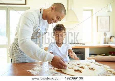 Father And Young Son Baking Cookies Together In The Kitchen