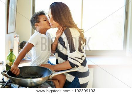 Smiling Mother Cooking And Getting A Kiss From Her Son