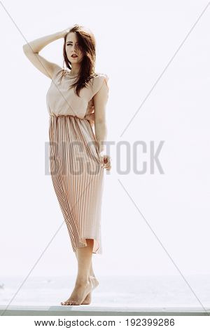 Fashionable clothing fashion and trends concept. Woman in long dress standing and posing barefoot.