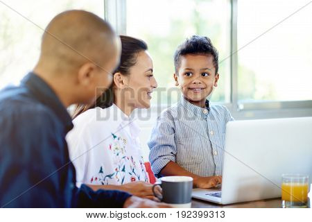 Happy Young Family Using A Laptop Together At Home