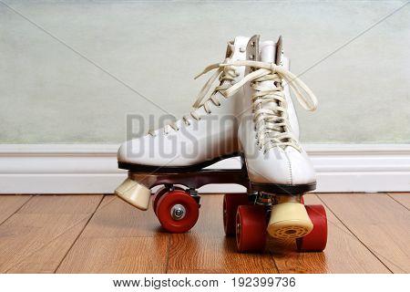 women white quad roller skates on wood floor
