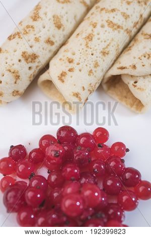 Bright saturated red currant berries and three pancakes lie diagonally on a white background close-up a virile frame