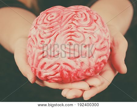 Woman hand holding brain. Having something on mind thinking of solution idea concept.