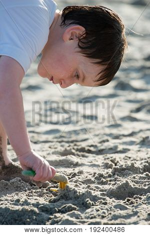 A Young little boy playing with the sand and building sandcastle at the beach near the sea.