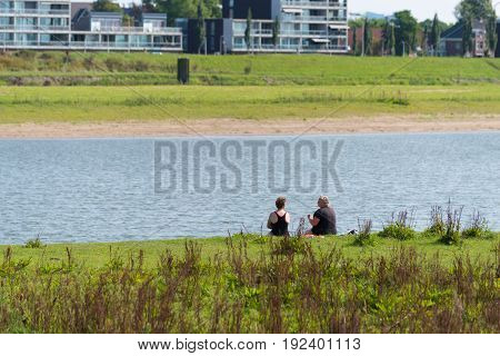 DEVENTER NETHERLANDS - AUGUST 27 2016: two unknown women sitting at a river